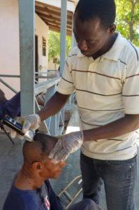 Member of Heartline's Outreach Team in Haiti trims the hair of an elderly man